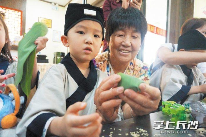 长沙小朋友穿汉服戴香囊包粽子 品味民俗文化