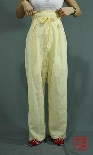 整理裤子,把裤子提到合适的高度,裤脚离地三公分左右