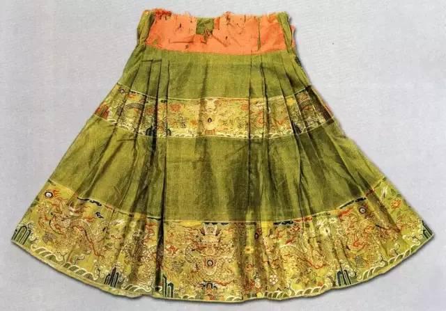 除裙子前后一块不加打褶外,其余诸处打褶,褶大而疏,缀于异色的裙腰上